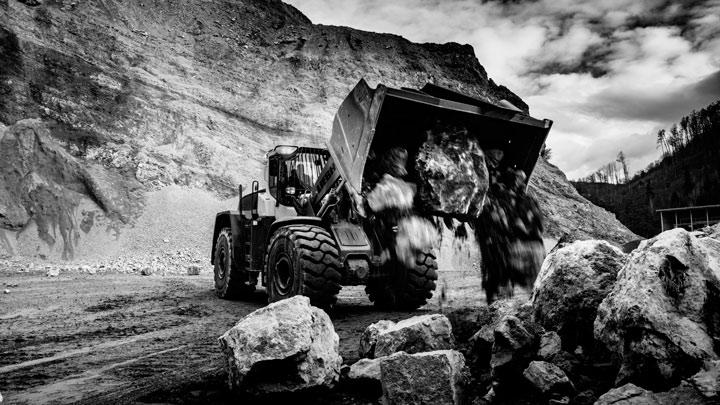 Челен товарач, разтоварващ твърди скали с кофа, изработена от износоустойчива стомана Hardox®.