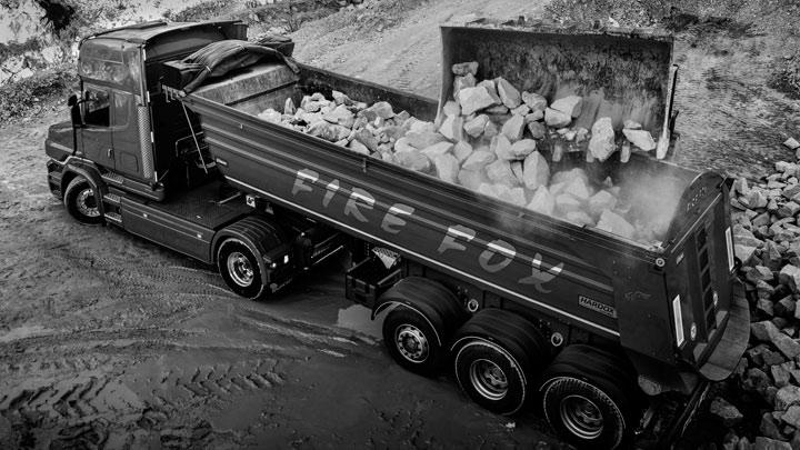 Огненочервен камион, натоварен с камъни. Камионът може да поеме повече полезен товар благодарение на високоякостната стомана Hardox®.