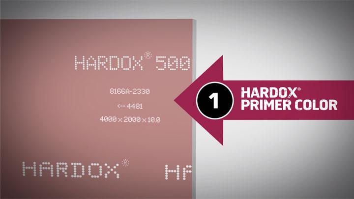Оригинален износоустойчив лист Hardox® с продуктови маркировки и характерния червен грунд.