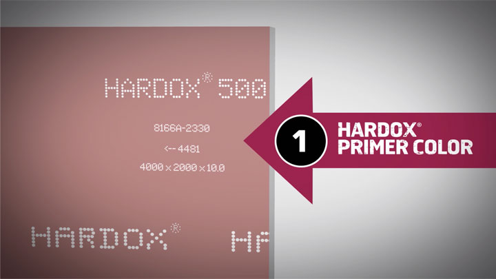 Genuine Hardox® wear plate, with product markings and its tell-tale red primer color.
