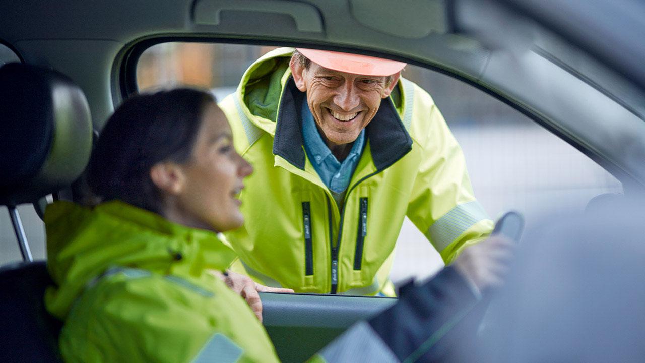 Frau im Auto spricht mit einem Mann draußen