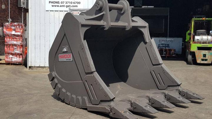 A big gray excavator bucket with the Hardox® In My Body logo.