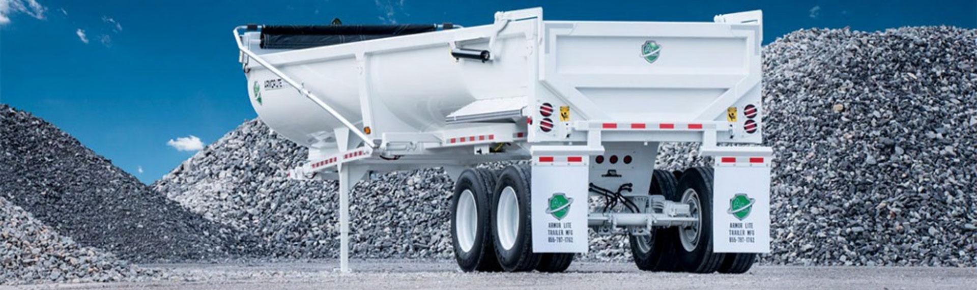 A white half-round dump trailer in steel bearing the Hardox In My Body logo.