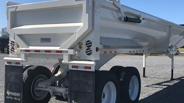 A white half-round dump trailer with the Hardox In My Body logo getting ready to hit the road