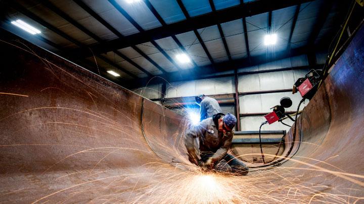 A welder at work deep inside the half round body of a dump semitipper.