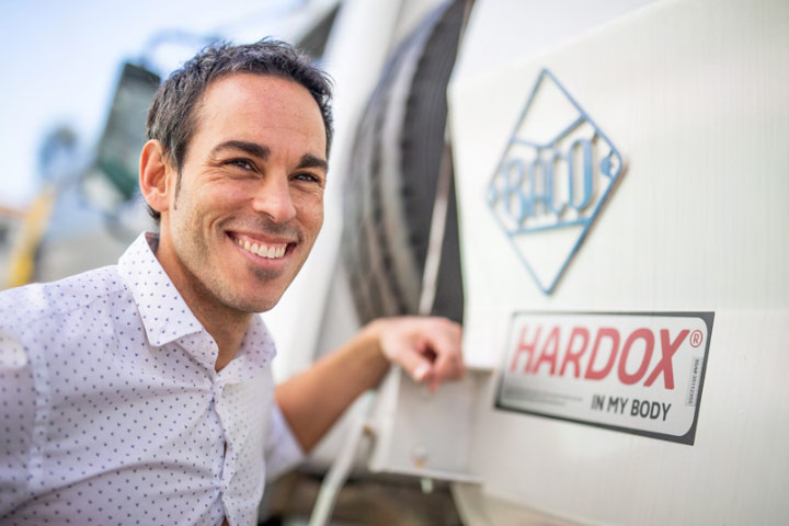 A smiling operations manager from Industrias Baco next to a truck with a Hardox® In My Body sign of quality.