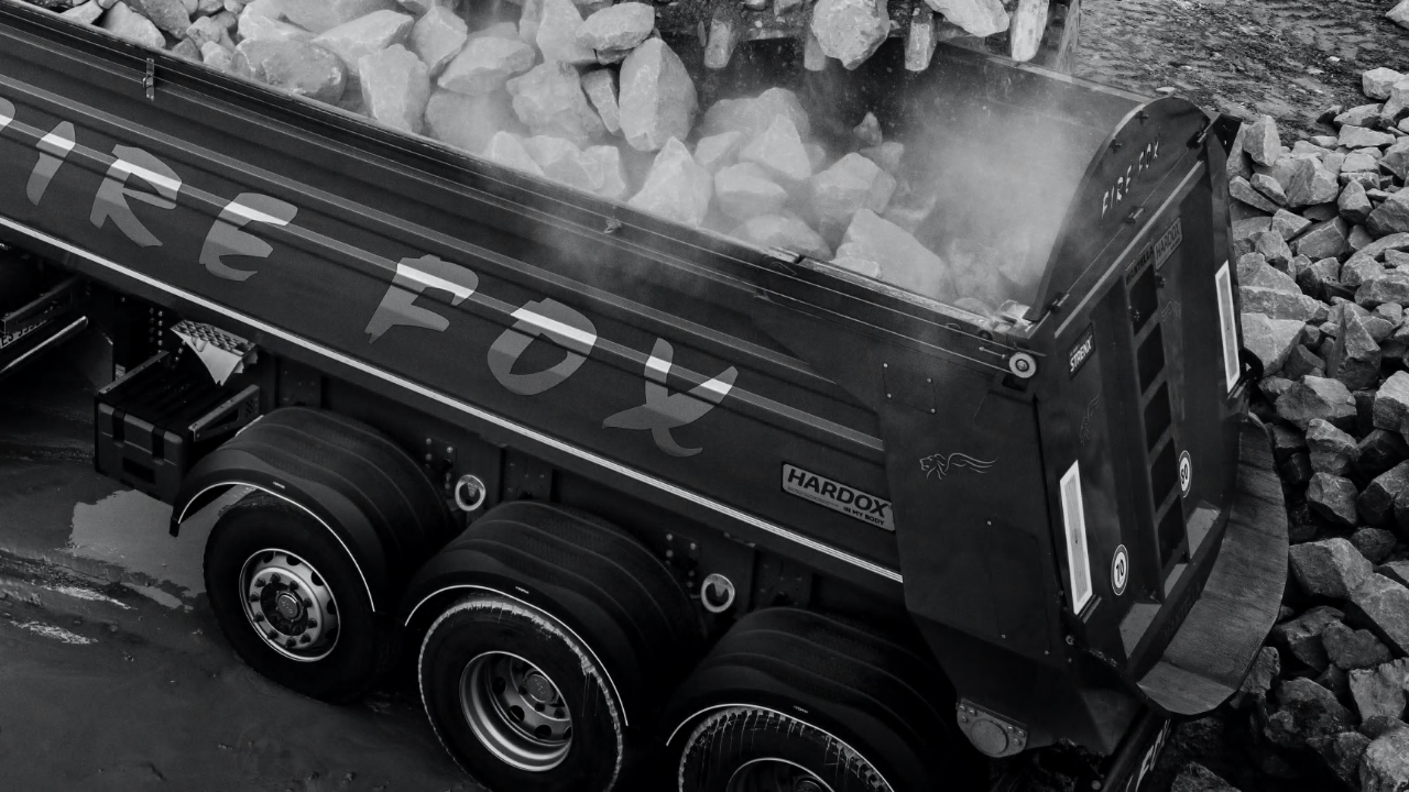 Black and white photo of the Firefox dumper body loaded with rocks, made in Hardox® 500 Tuf wear plate.