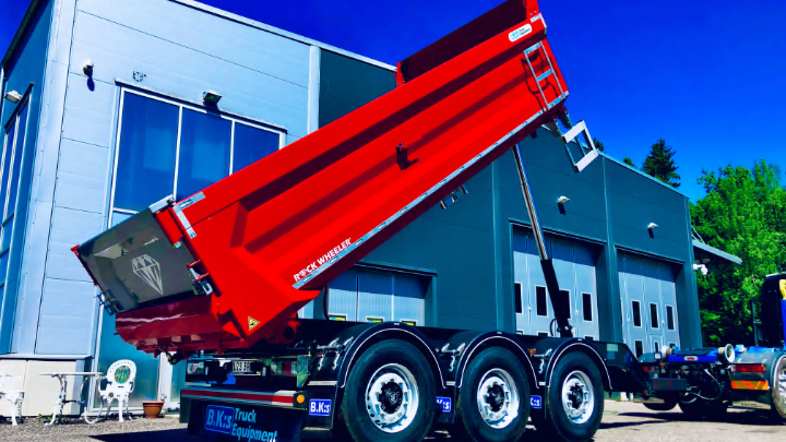 A bright red dump truck trailer with a body in Hardox® 500 Tuf outside  B.K:s' facility being tipped.