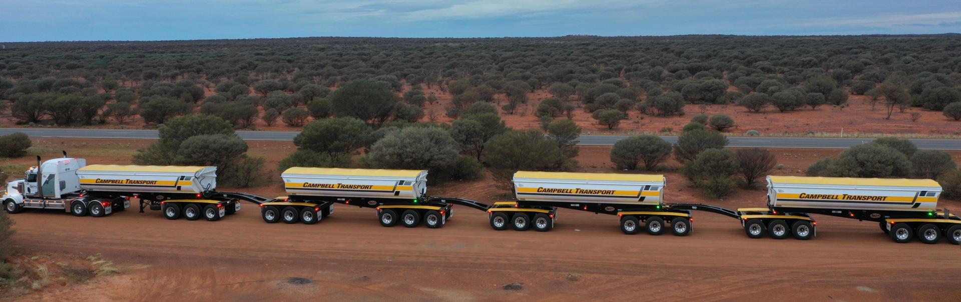 A road train of side dump trailers in Australia
