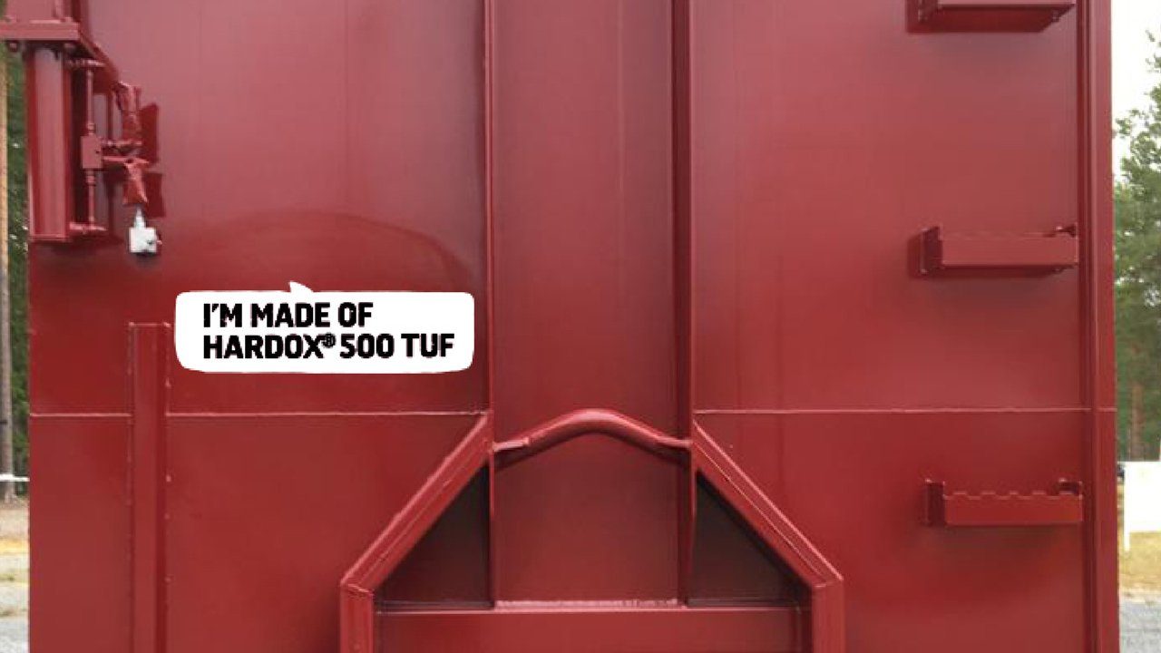 """A bright red hooklift container saying """"I'm made of Hardox 500 Tuf""""."""