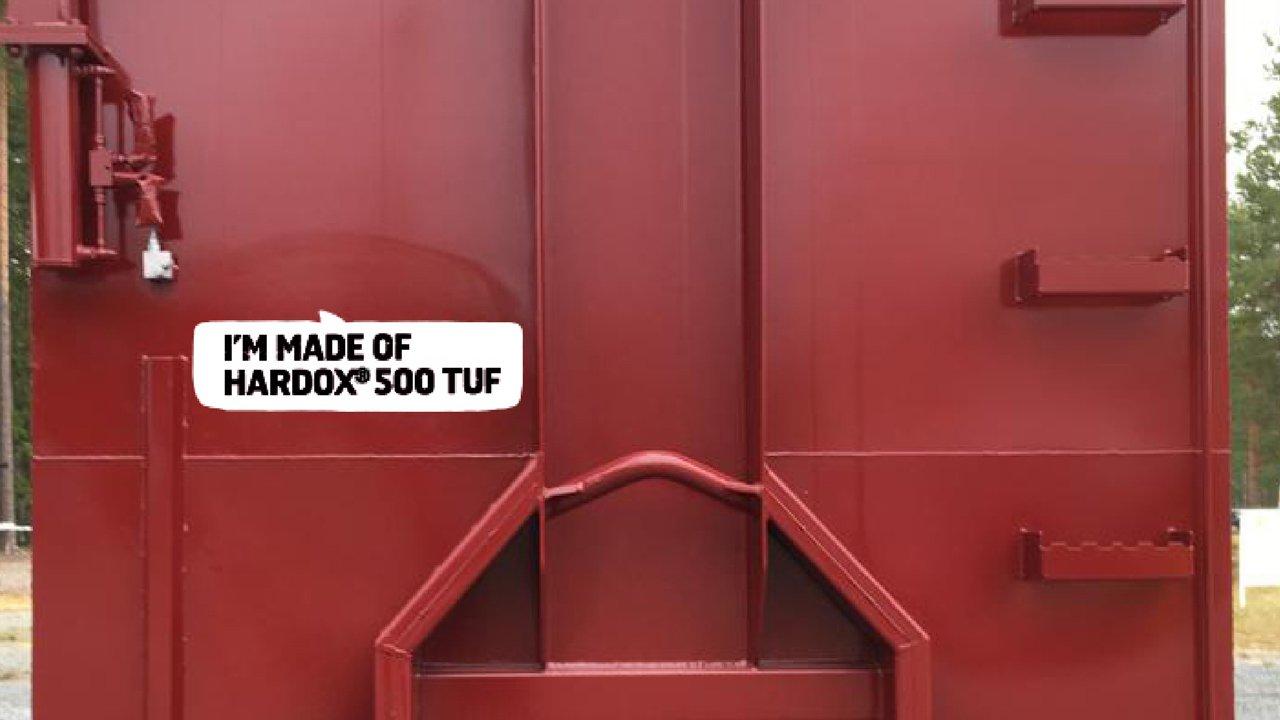 """Ein leuchtend roter Abrollcontainer mit der Aufschrift """"Ich bestehe aus Hardox 500 Tuf""""."""