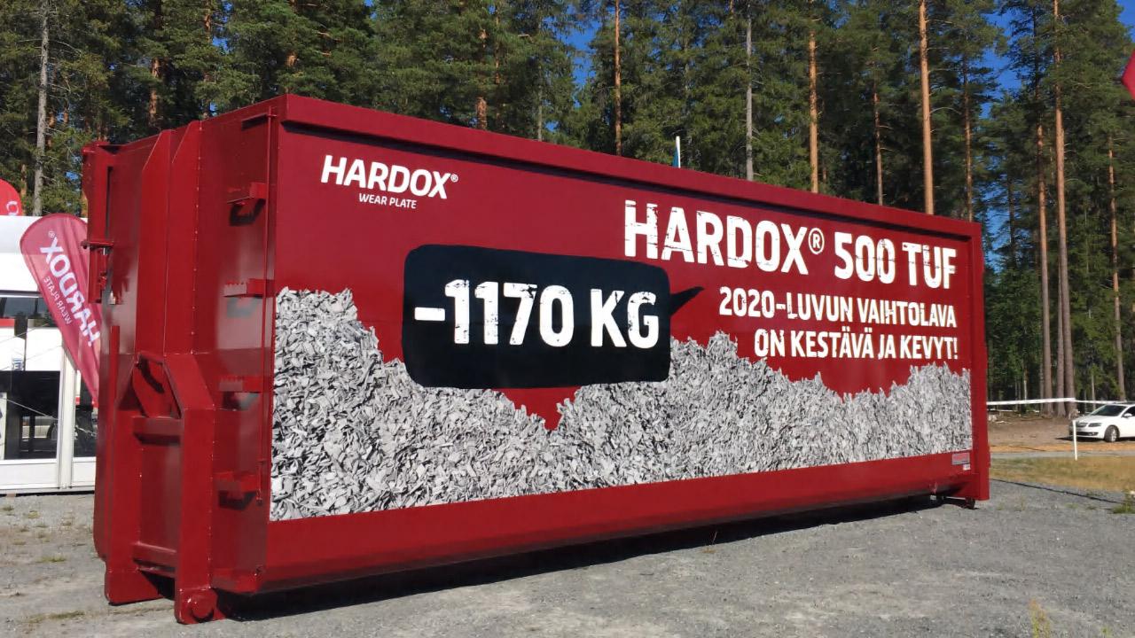 Světle červený ocelový kontejner z oceli Hardox 500 Tuf stojící v lese.