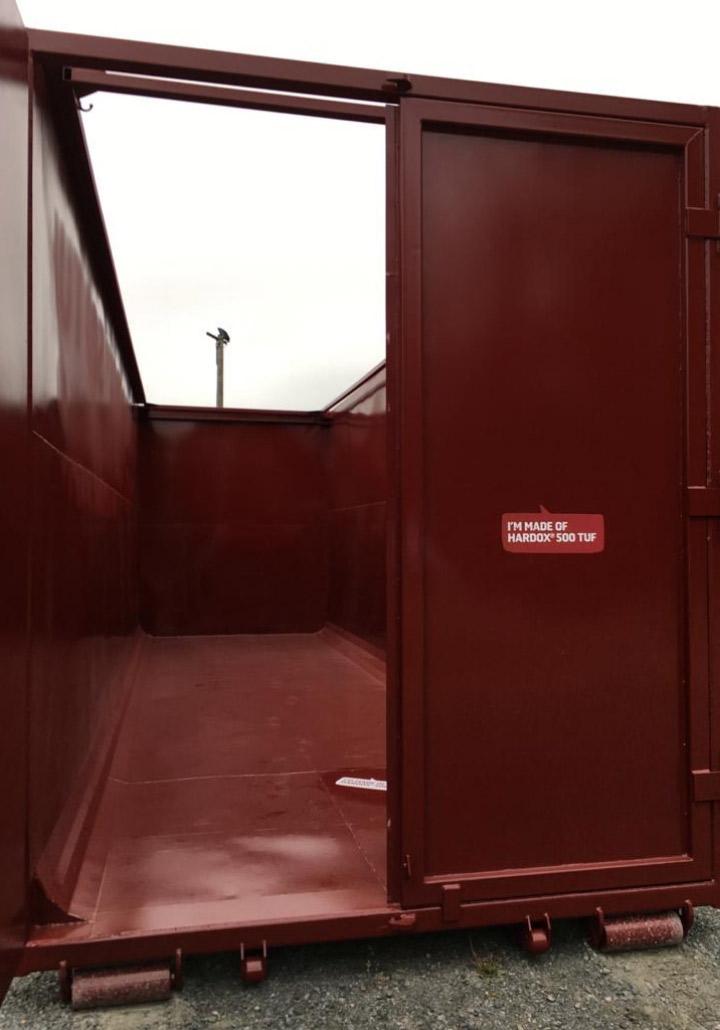 Uma porta abrindo em um contêiner de aço feito com o aço Hardox® 500 Tuf sólido e resistente.