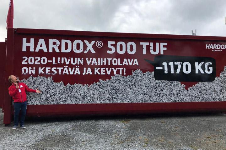 Un contenedor de acero de color rojo brillante en un bosque, fabricado con acero Hardox® 500 Tuf, con una inscripción en finlandés.