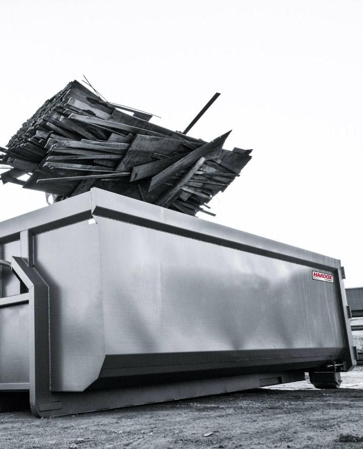 """Ein Abrollcontainer aus Stahl mit dem """"Hardox® In My Body""""-Aufkleber kann Schläge vertragen, ohne dass sein Verhalten stark beeinträchtigt wird."""