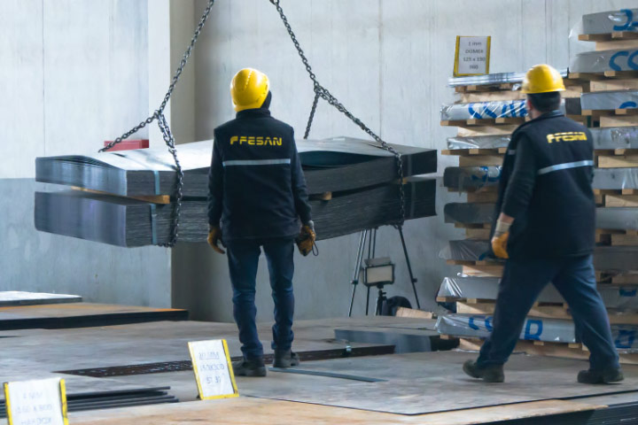 Two people in yellow hard hats supervising a delivery of Hardox® wear plate