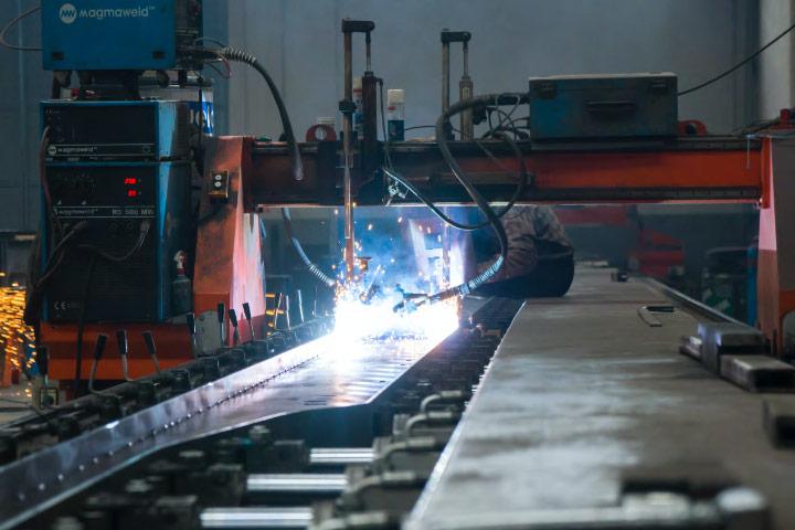 A welder in a workshop, welding a thin yet strong sheet of Hardox® wear plate.
