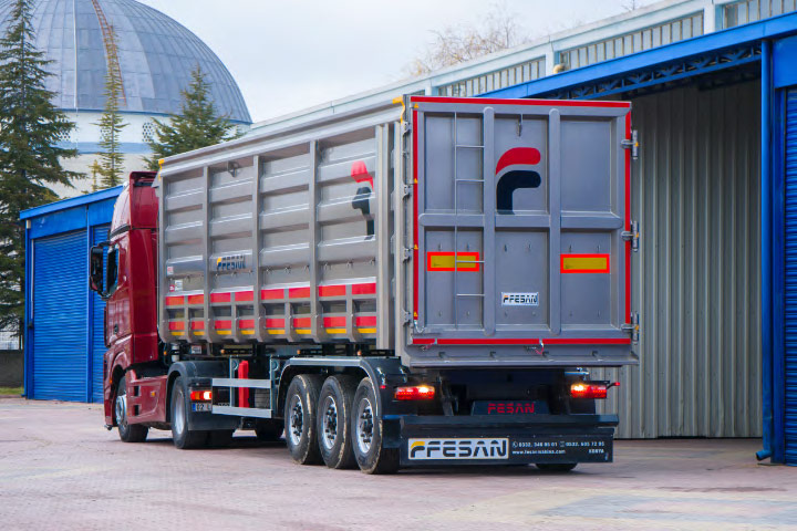 A silver and red dumper trailer made by Fesan coming out of a warehouse.