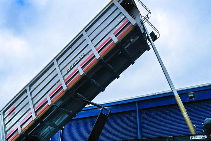 A dump trailer body made in Hardox® 500 Tuf, lifted high against a blue sky.