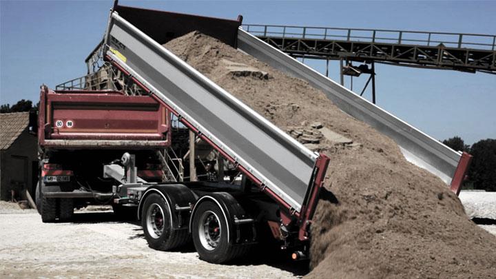 Un cassone ribaltabile a pianale aperto che scarica un carico pesante di sporco e rocce.