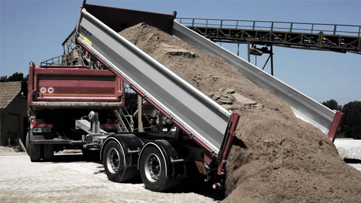 An open-bed tipper body dumping out a heavy load of dirt and rocks.