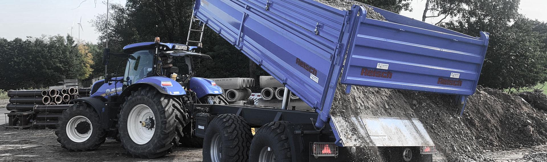 En blå tippvagn med flak i Hardox® stålplåt som tippar ut en last med sten.