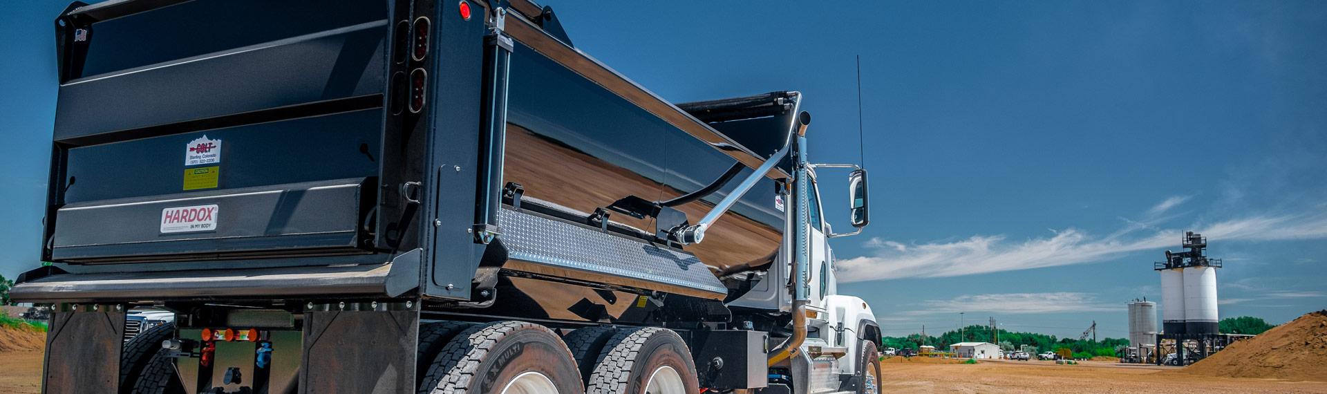 A truck with dump body bearing the Hardox In My Body logo.