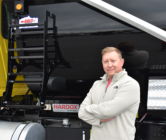 The general manager of Industrial Welding Supply standing in front of a Colt-branded and Hardox® in My Body-certified custom truck body.