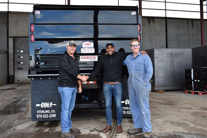 Three smiling men in front of the first Colt-branded dump truck made of Hardox® 500 Tuf, from Industrial Welding Supply.