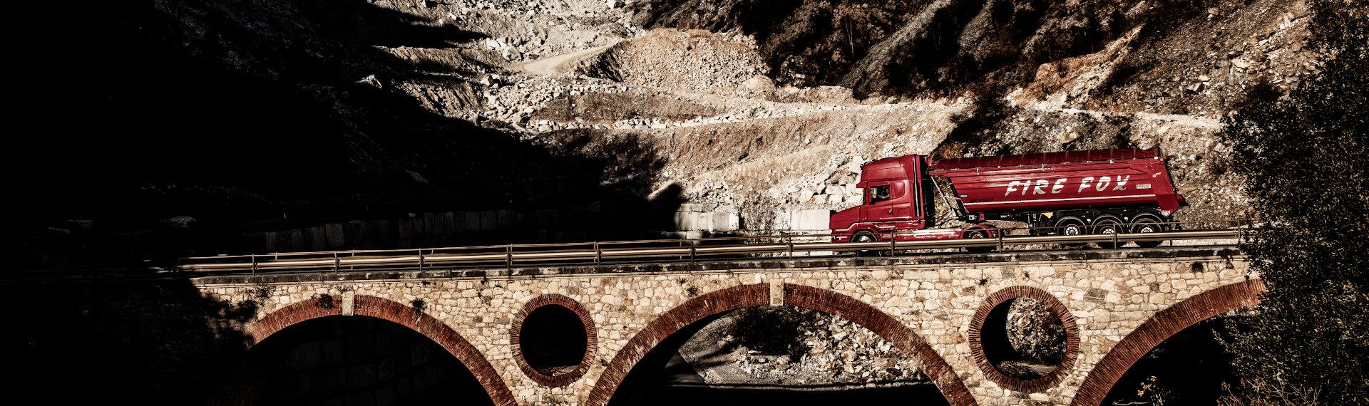 Ohnivě rudý nákladní vůz Fire Fox vyrobený z ocelového plechu Hardox 500 Tuf přejíždí most