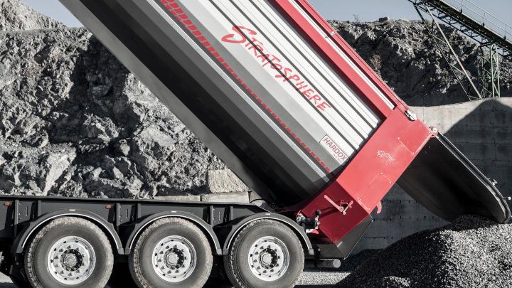 내마모 강재인 Hardox 500 Tuf 제품으로 제작된 빨간색 Stratosphere 덤프 트럭 적재함이 적재물을 쏟아내고 있는 모습