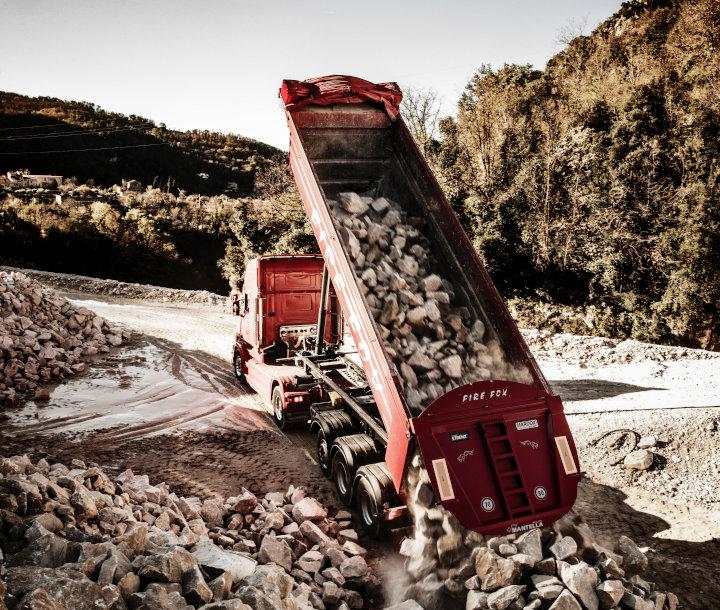 Hardox 내마모 강판으로 제작된 밝은 빨간색의 Fire Fox 덤프 트럭이 거친 암석을 쏟아내고 있음