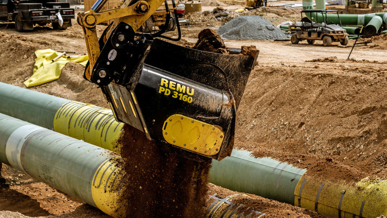 A screening bucket empties soil over pipework on a construction site