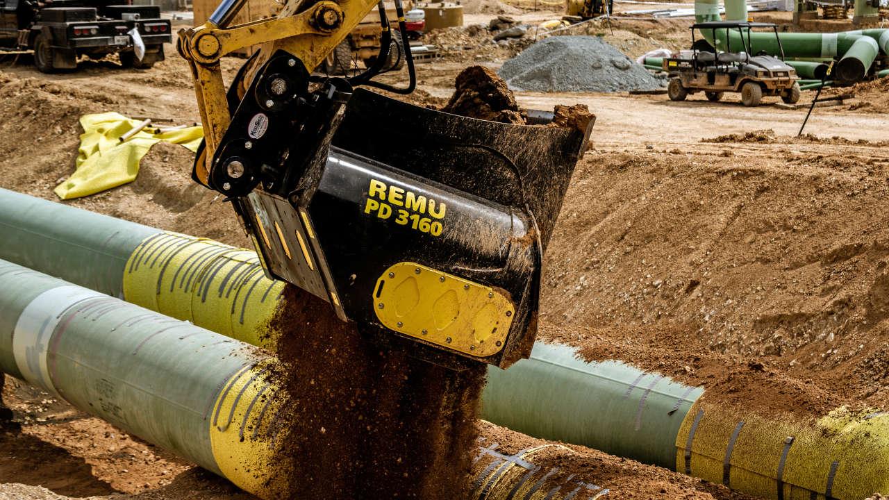 Ein Sieblöffel füllt Erde über Rohrleitungen auf einer Baustelle