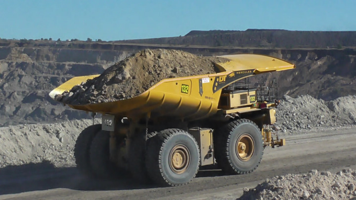 A yellow mine dump truck on the road with a heavy load
