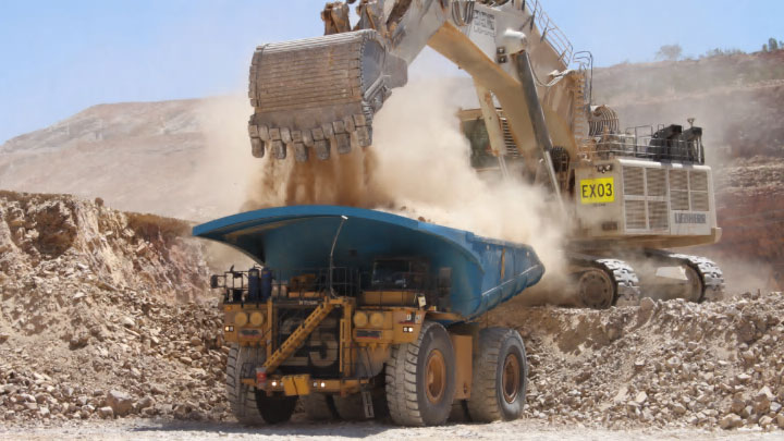Camion da miniera per l'estrazione a cielo aperto mentre carica la roccia