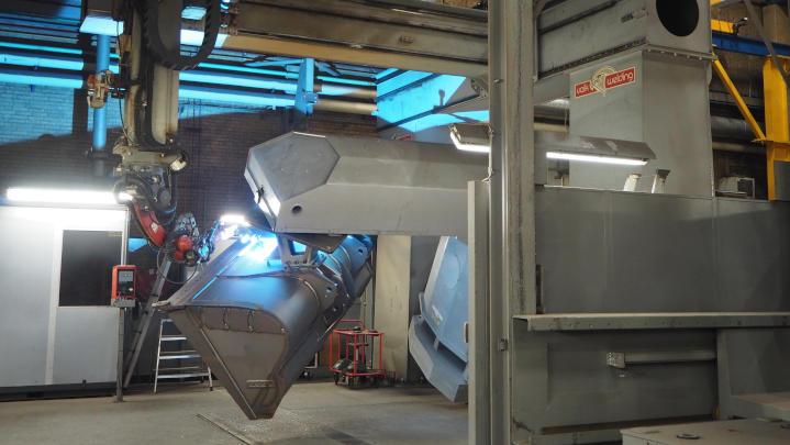 A custom excavator bucket being built using robotic welding
