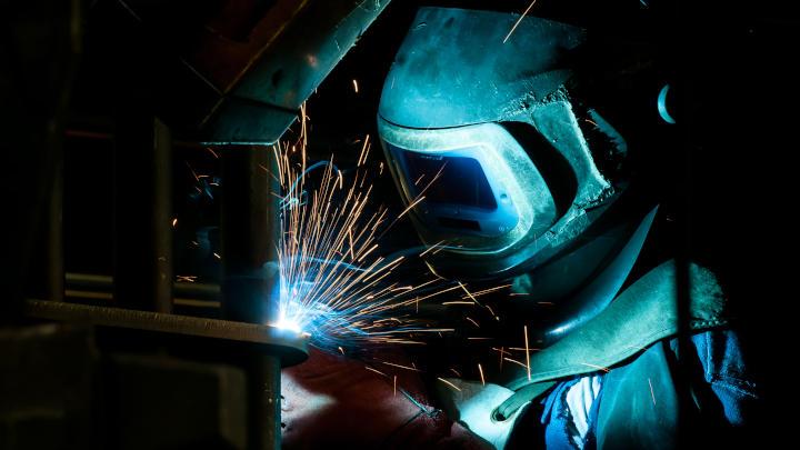 Un soldador aplica el soplete en un cangilón adaptado para excavadora, fabricado con Hardox® 500 Tuf