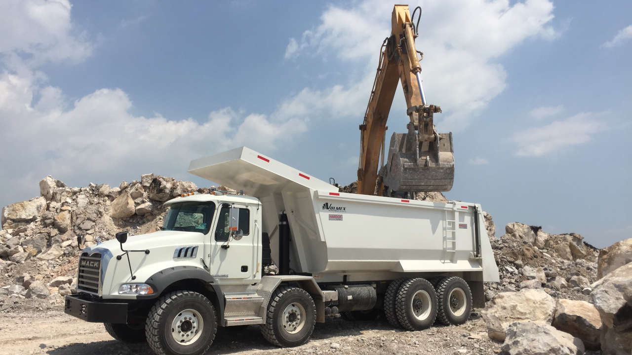 Rocks being loaded into a strong and tough dump truck on a mining site.
