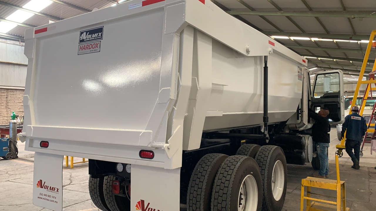 A shiny white dump truck body with the Hardox® In My Body decal on it.