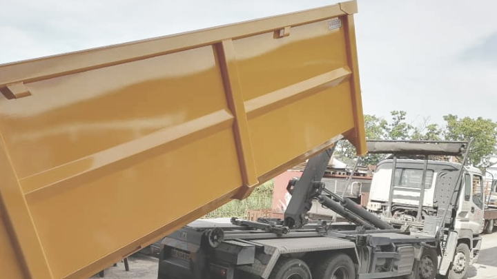 A dump truck tipping a bright yellow waste container body that is built in corrosion resistant steel.