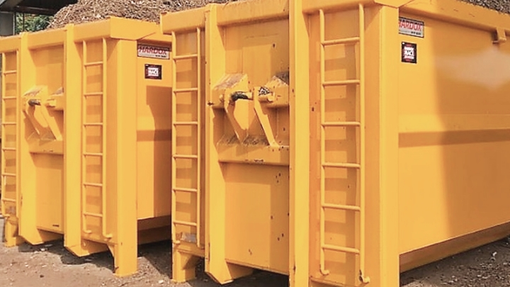 Two yellow open-top containers filled with corrosive wood chips and bearing the Hardox® In My Body sign of quality.