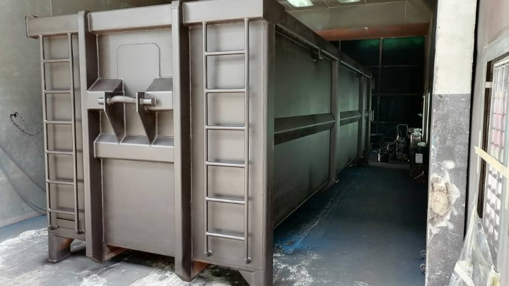 A gray waste container body with tailgate and door made in Hardox® HiAce, a corrosion resistant steel.