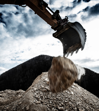 An excavator bucket with a high-strength steel tube component taking the impact of a huge rock