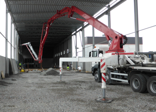Bright red boom on a slurry truck with parts that use abrasion resistant steel pipe and tube in Hardox® steel