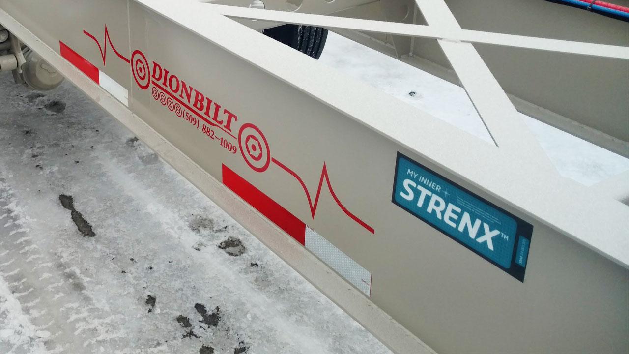 Közelkép egy My Inner Strenx jelöléssel ellátott fehér színű pótkocsi hossztartóról