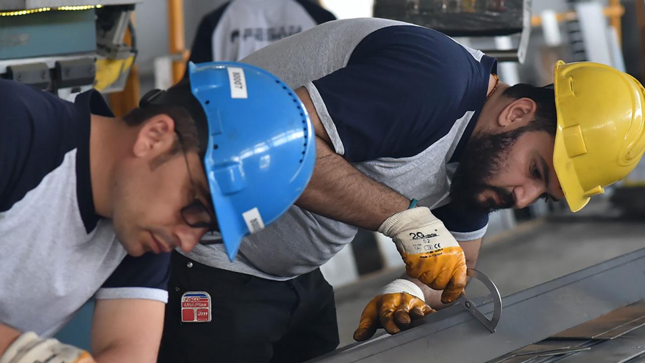 Két, védősisakot viselő munkás dolgozik egy nagy szilárdságú Strenx® acéllemezen.