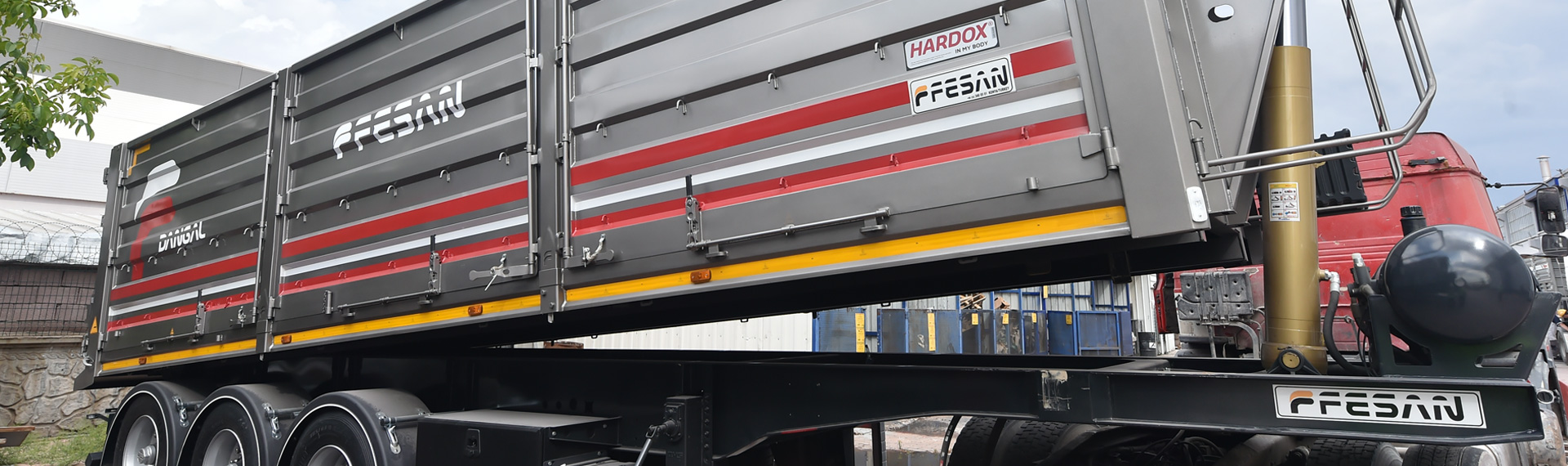 A shiny gray and red semitrailer dumper with the Fesan and Hardox® in My Body logos.