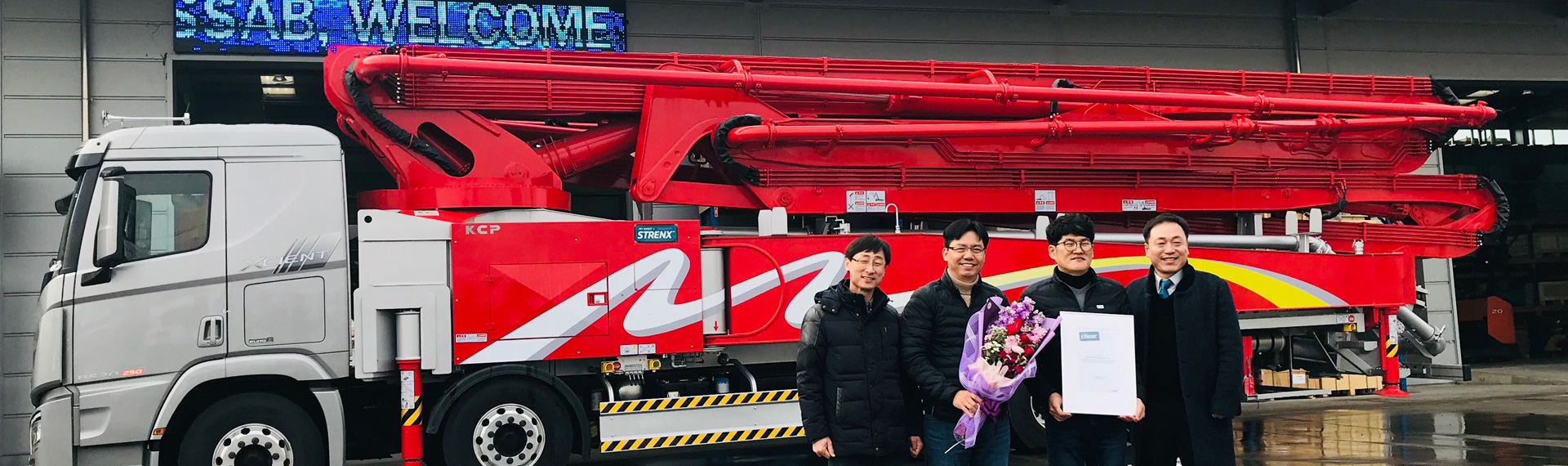 Bright red concrete pump truck with employees from KCP proudly holding a my Inner Strenx certificate
