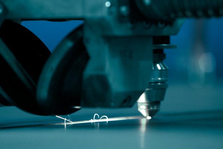 Bir lazer kesim başlığı, Strenx çelikten bir plakayı kesiyor.